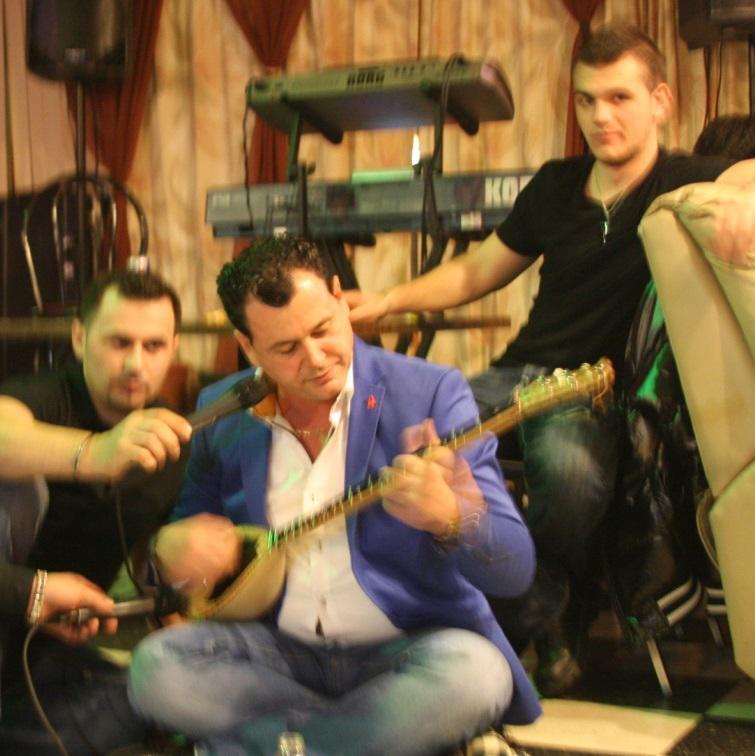"""Ne foto: Marash Bardheci duke interpretuar ne nje aksion te Kafe """" KUVENDI"""", Leonardi prapa dhe kengetari Zef Duhani duke i mbajtur mikrofonin."""